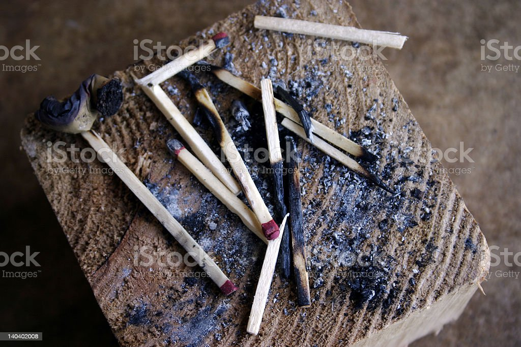 Burnt matches and ash on a wooden block royalty-free stock photo