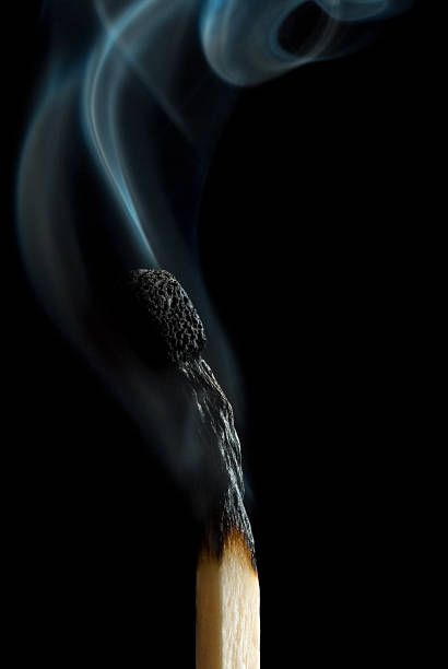 A burnt out match smoking on a black background stock photo