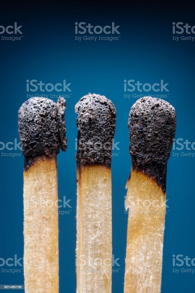 Burnt out safety matches. Blue background. stock photo