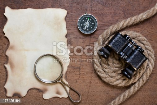 istock Burnt paper, compass, magnifying glass, binoculars, rope on wood 177426184