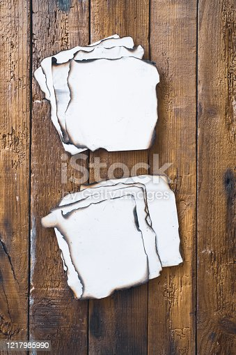 Burnt paper pieces on rustic plank background.