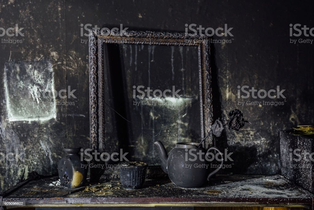 Burnt room interior. Burnt still life. Charred wall, picture frame, pot with burned rose in black soot stock photo