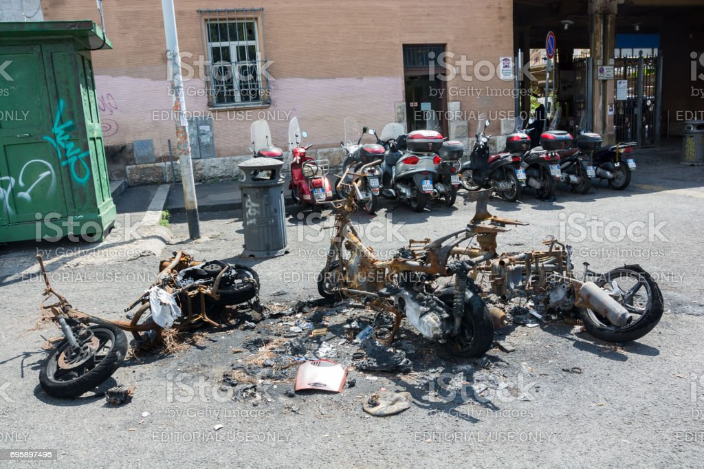 ROME, ITALY - AUGUST 17 2015: Burnt scooter in front of a railway station, Rome stock photo