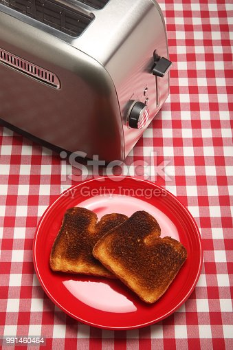 This is a close up photograph of two burnt slices of toast siting on a red plate next to a chrome toaster on a red and white checkered picnic table cloth.