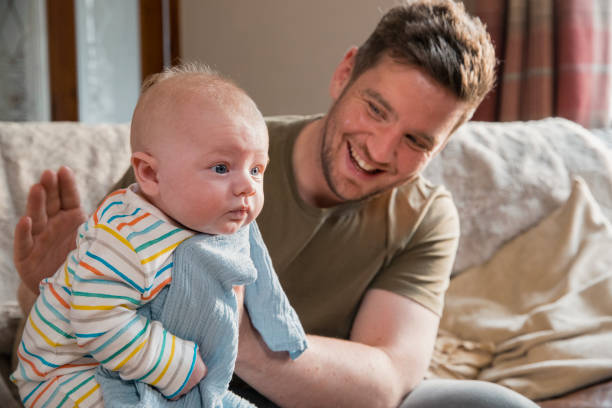 Burping the Baby After Feeding Father sitting on the edge of the sofa in the living room and burping her newborn child after feeding him. stay at home father stock pictures, royalty-free photos & images
