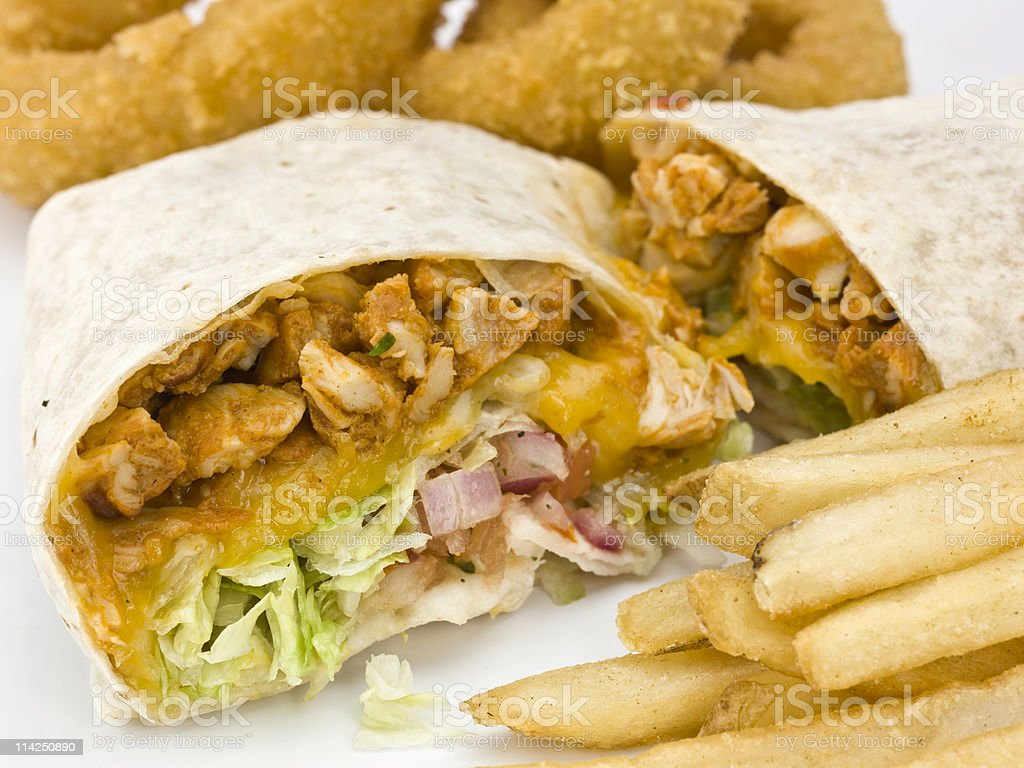 Burrito on a plate with French fries and onion rings. stock photo