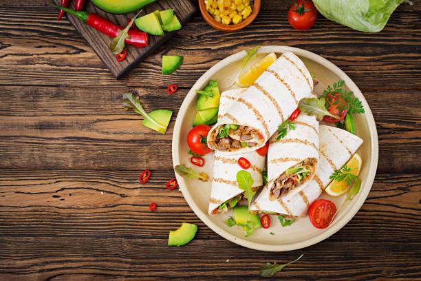 부리는 나무 바탕에 야채와 쇠고기를 래핑합니다. 쇠고기 버 리 토, 멕시코 음식입니다. 건강 한 음식 배경입니다. 멕시코 요리입니다. 최고의 볼 수 있습니다. - 굴리기 뉴스 사진 이미지