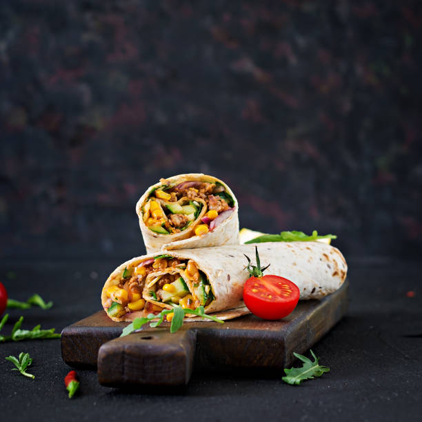 burritos wraps with beef and vegetables on  black background. beef burrito, mexican food. - tortilla stock photos and pictures