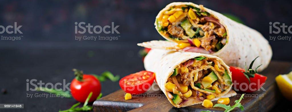 Burritos wraps mit Rindfleisch und Gemüse auf schwarzem Hintergrund. Rindfleisch-Burrito, mexikanisches Essen. – Foto