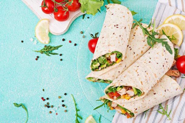 burritos wraps mit huhn und gemüse auf hellem hintergrund. huhn burrito, mexikanisches essen. ansicht von oben flach legen - veggie wraps stock-fotos und bilder