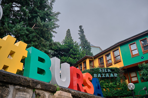 Bursa Yesil district during overcast and cloudy day with colorful BURSA with hashtag symbol.