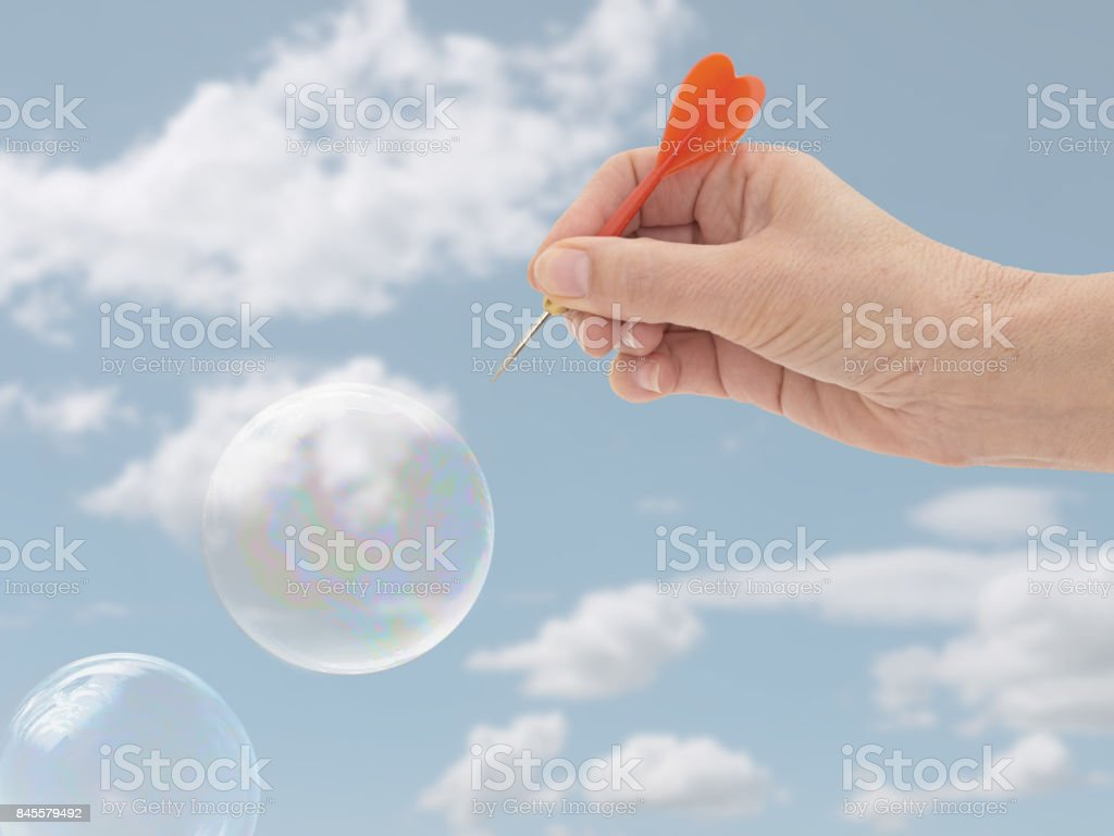 Burst my bubble. Financial or general concept. Woman's hand. stock photo