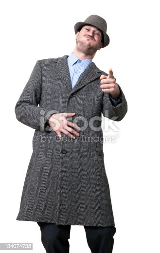 A young adult male wearing an overcoat and a maching hat, looking and pointing at the camera bursting with laughter..Isolated on white background.