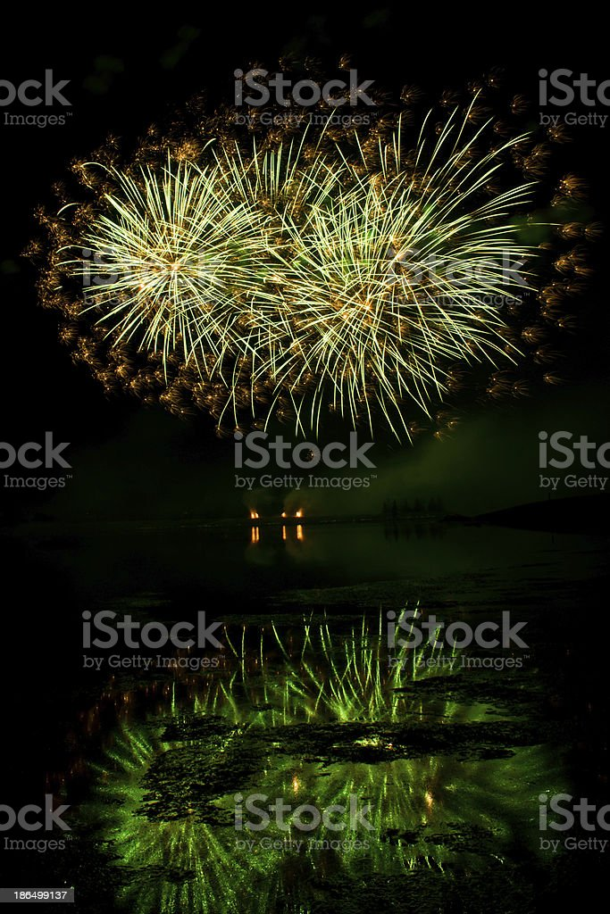 Bursts of Green and Orange Fireworks royalty-free stock photo