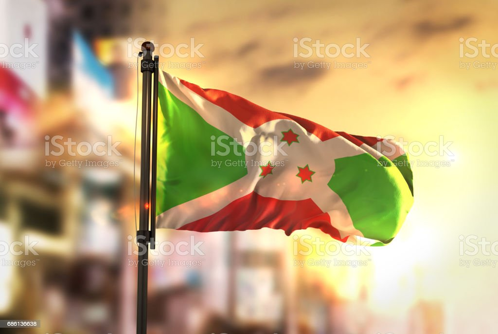 Burundi Flag Against City Blurred Background At Sunrise Backlight stock photo