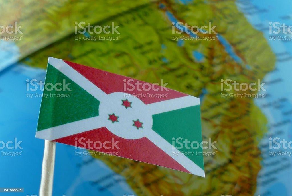 Burundi flag with a globe map as a background macro stock photo