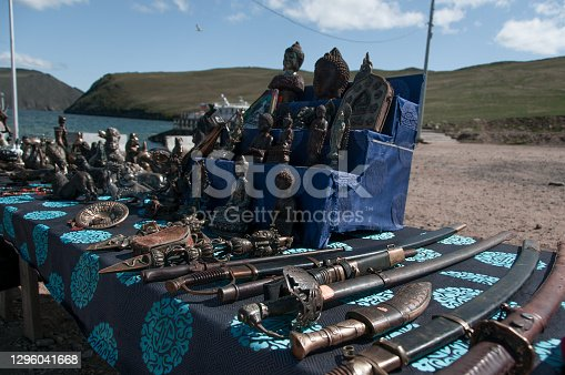 Buryat souvenirs: edged weapons, figurines, dishes on the shore of Lake Baikal close-up