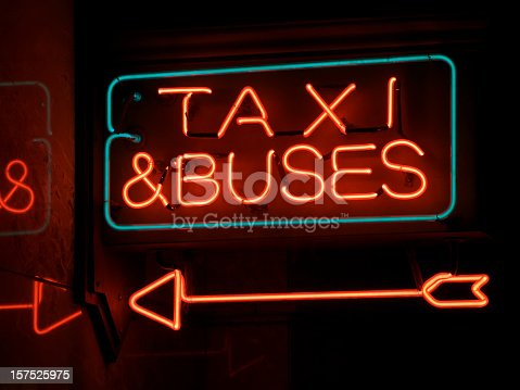 A Neon sign showing direction to go for a Bus or Taxi. Electric sign is illuminated with a partial reflection on the wall.