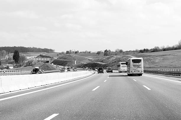 Bus cars and trucks on busy autobahn Stuttgart, Germany - March 26, 2016: Black and white image of busy bundesautobahn or Federal Motorway highway with busy traffic on a spring day with beautiful green fields and blue clouds singen stock pictures, royalty-free photos & images