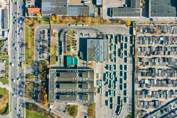 bus depot with garages and parked buses, manufacturing buildings and warehouses. aerial photo of city industrial area stock photo