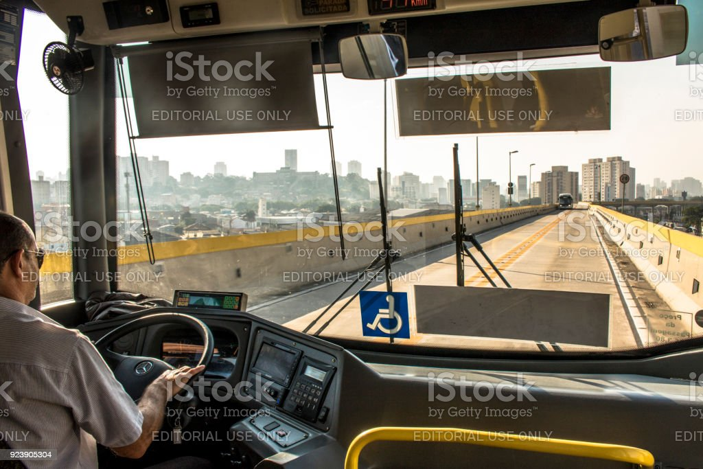 Bus driver drives an articulated bus stock photo