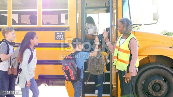 A senior female bus driver greets each child boarding the school bus with a high-five.