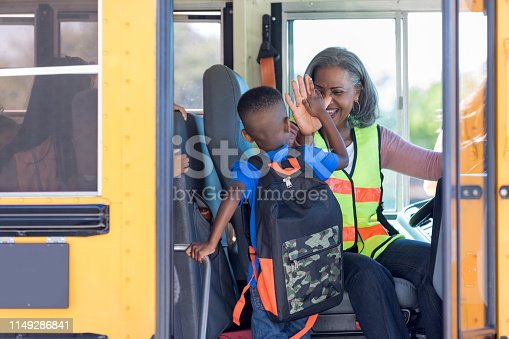 On the first day of school, a mature adult bus driver welcomes a new first grader by giving him a high five.