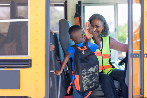 Bus driver high fives new student stepping on bus stock photo