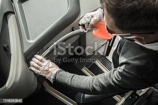 Caucasian Intercity Bus Driver Sanitizing Railings Using Alcohol in Spray. Preparing Moto Coach For Another Trip of the Day.