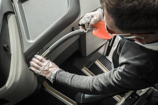 Bus Driver Sanitizing Railings Using Alcohol in Spray stock photo
