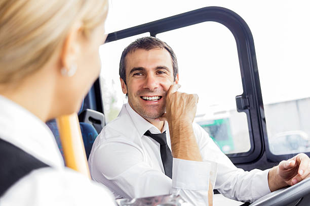 Bus driver talking to the passenger. stock photo