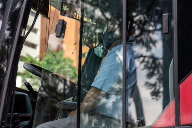 Busfahrer mit Maske an einer Ampel geparkt. Bogotá. Kolumbien. – Foto