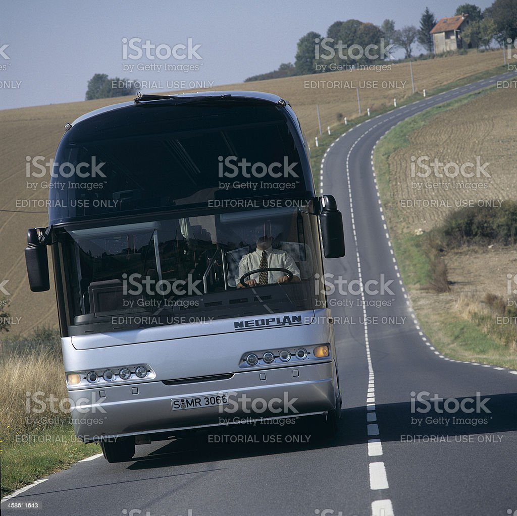 Bus driving on a country road stock photo