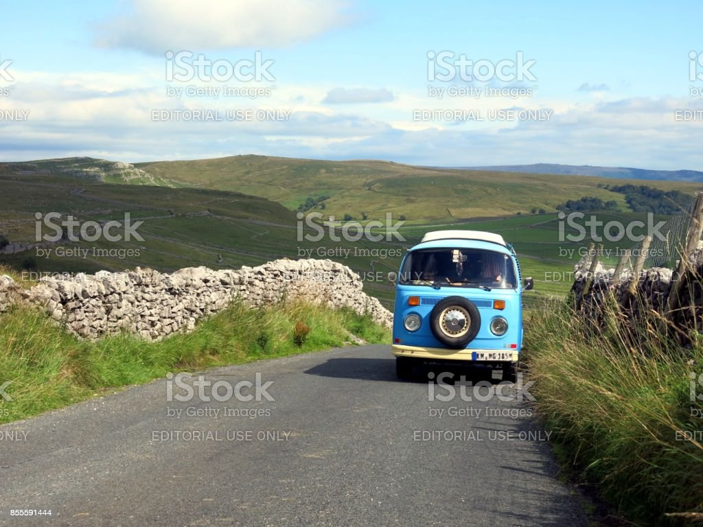VW Bus driving on narrow countryroad in England stock photo