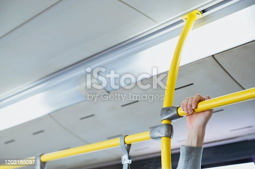 Unrecognisable person holding onto a bus handrail.