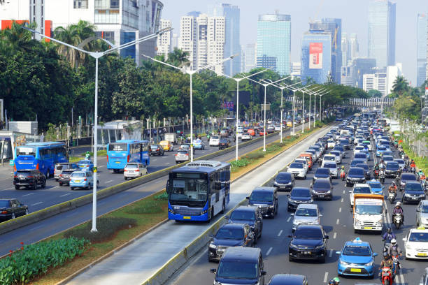 bus rapid transit in heavy traffic road at jakarta city Brt jakarta called as transjakarta passes on jendral sudirman street in heavy traffic on weekdays. bus rapid transit stock pictures, royalty-free photos & images