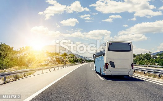 Tourist bus rushes along the asphalt high-speed highway.