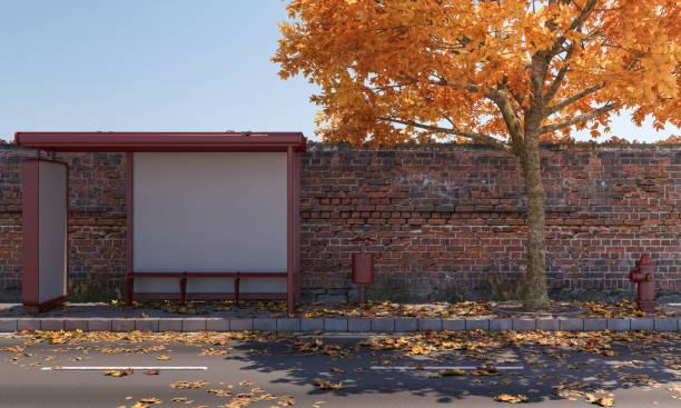 Abrigo de ônibus na frente de uma parede de tijolos - foto de acervo