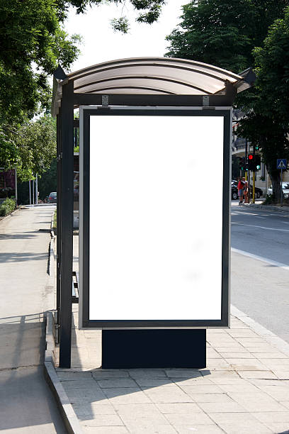 bus shelter on the side of the street on a sunny day - bushalte stockfoto's en -beelden