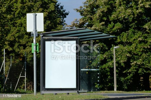 841502736 istock photo bus stop and bus shelter with white blank advertisement panel 1175443910