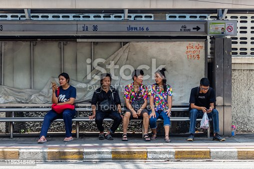 Bangkok, Thailand - April 13, 2019: Local people waiting for the bus on a public transportation stop in central Bangkok