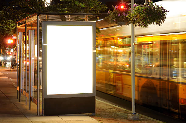 Bus Stop Billboard at Night Bus stop billboard at night. Blank advertising space, traffic lights electronic billboard stock pictures, royalty-free photos & images