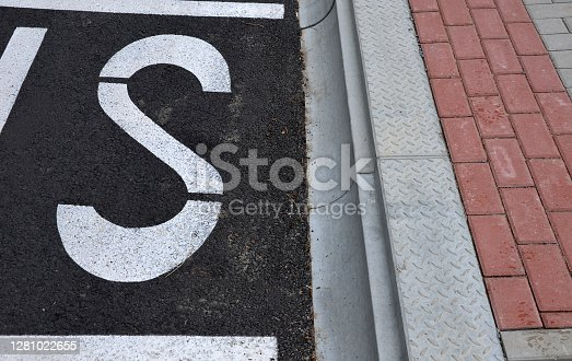 bus, stop, consisting, reserved, place, word, bus, Horizontal, traffic, sign, white, line, lines, concrete, curb, rounded, damage, sidewall, tire, paving, blind, paving, bump, bumps, guide, edge, station, asphalt, road, street, tilled, tiled, tiller, floor, pavement, Parking, bay, pebble, pebbles, mulch, lawn, curb, curbs, fence, private, black, gray, lengthwise, raised