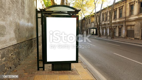 istock Bus stop in city with empty white mock up banner for advertising, clear public information board in urban setting in sunny summer day, blank billboard with copy space section for informational message 1067325636