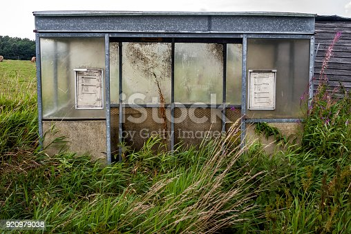 Old overgrown and weathered abandoned bustop in rural landscape