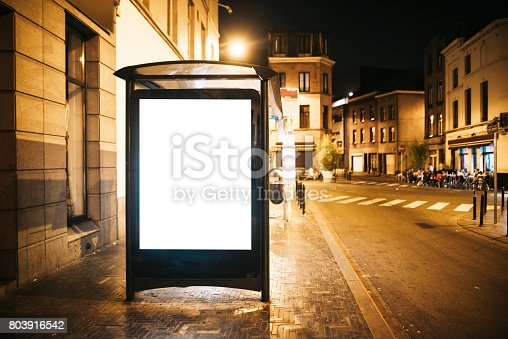 istock Bus stop with blank billboard at night 803916542