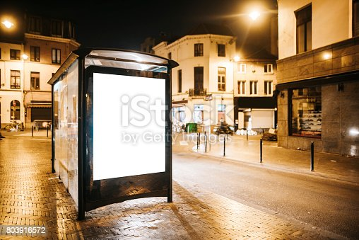 istock Bus stop with blank billboard at night 803916572