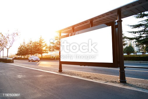841502736 istock photo Bus stop with blank billboard at sunset 1192500931