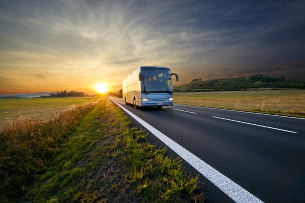 autobuses viajan por la carretera de asfalto en paisaje rural al atardecer - autobús fotografías e imágenes de stock