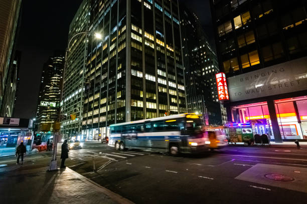 Bus traveling through Wall Street intersection in New York City at night stock photo